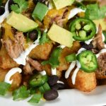 pulled pork totchos recipe in a white bowl and ready to eat