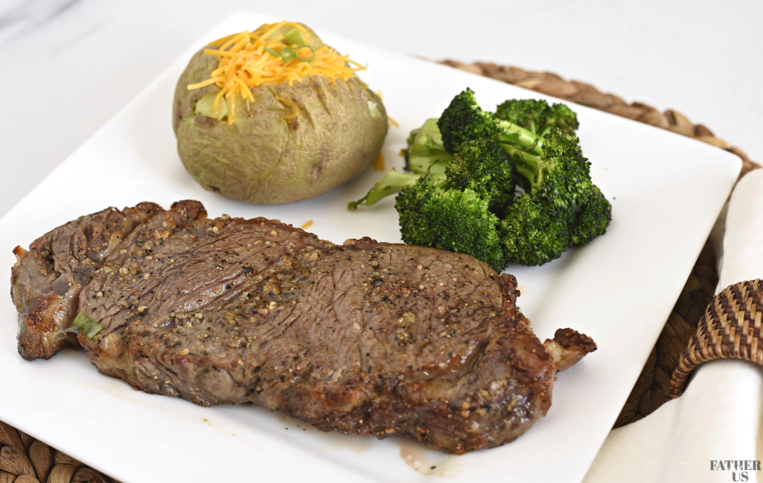 Air Fryer Steak Recipe on a plate with a baked potato and broccoli.