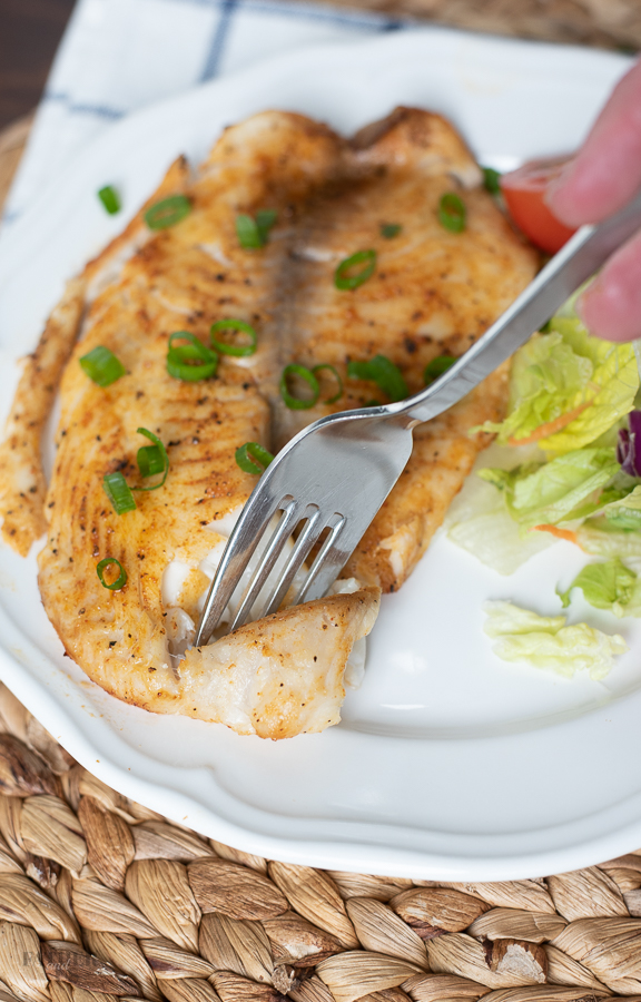 Air Fried Tilapia being served for dinner with a healthy side salad.