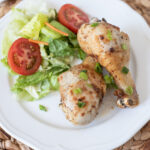 Air Fryer Drumsticks being served with a fresh side salad.