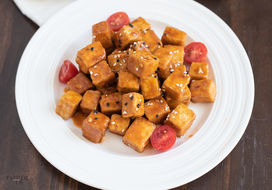 Air Fryer Tofu made with a sweet and spicy sauce being served on a white plate.